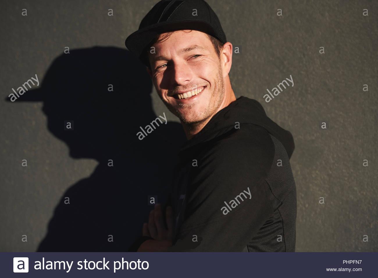 Portrait of man wearing baseball cap smiling - Stock Image
