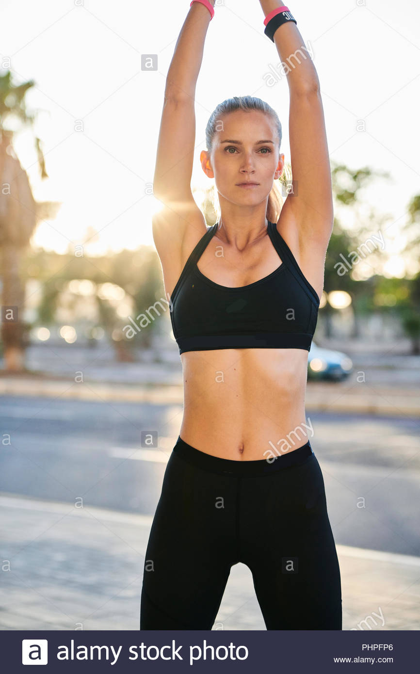 Woman wearing sports bra with her arms raised - Stock Image