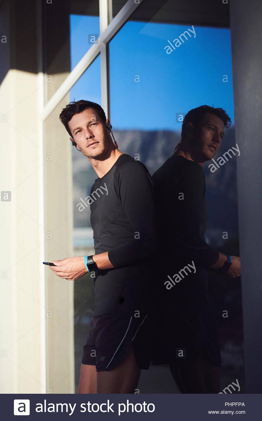 Man using smart phone by window Stock Photo