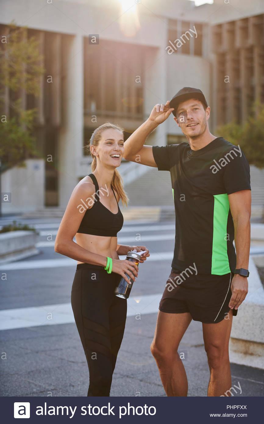 Couple wearing sportswear in public square - Stock Image