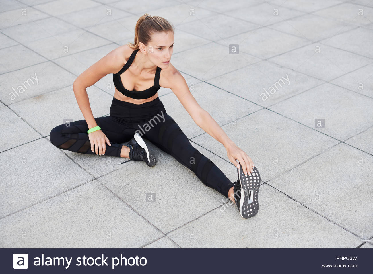 Woman wearing black sportswear stretching on footpath - Stock Image