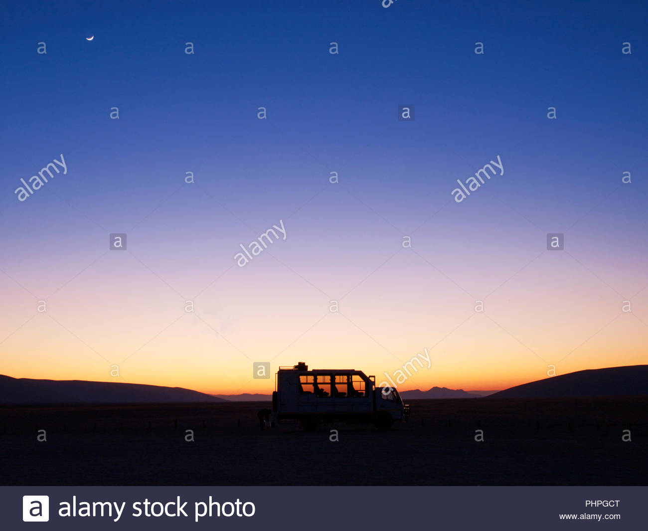 Tour bus in desert at sunset - Stock Image