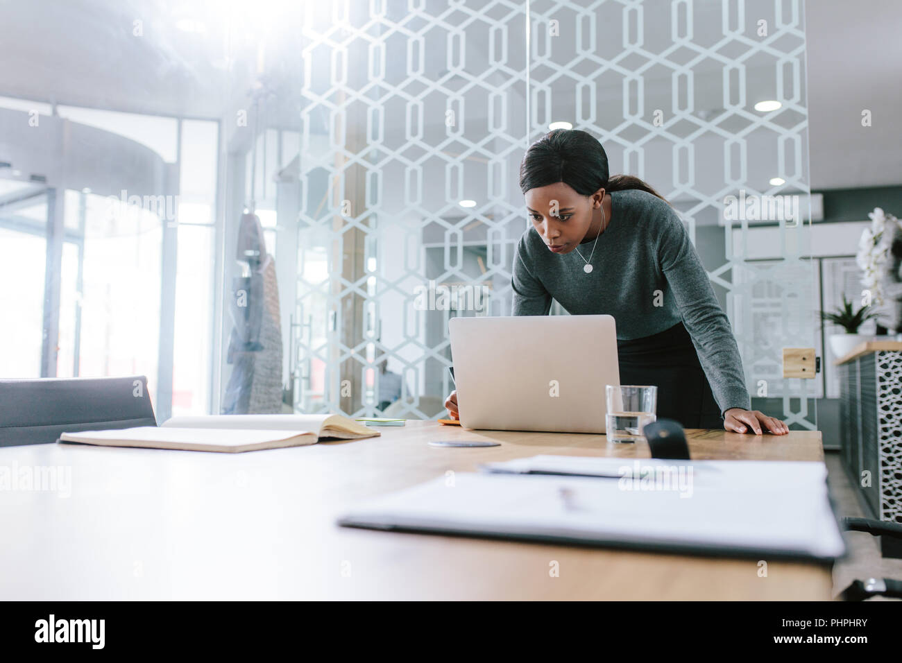 African woman standing by conference table and looking at her laptop. Business woman working on laptop computer in boardroom. - Stock Image