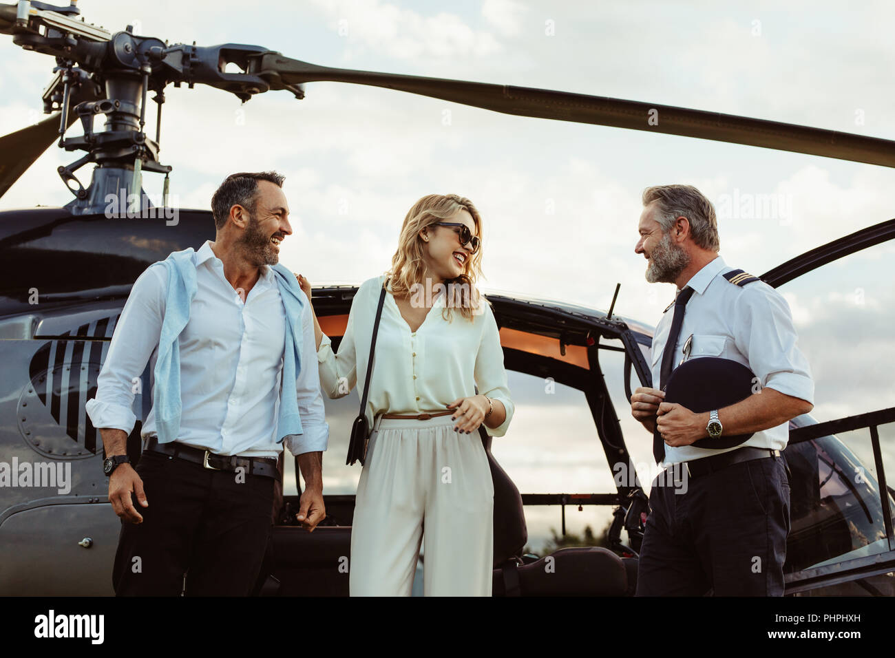 Smiling couple alighted from a private helicopter talking to the pilot. Couple getting off a private aircraft with mature pilot. - Stock Image