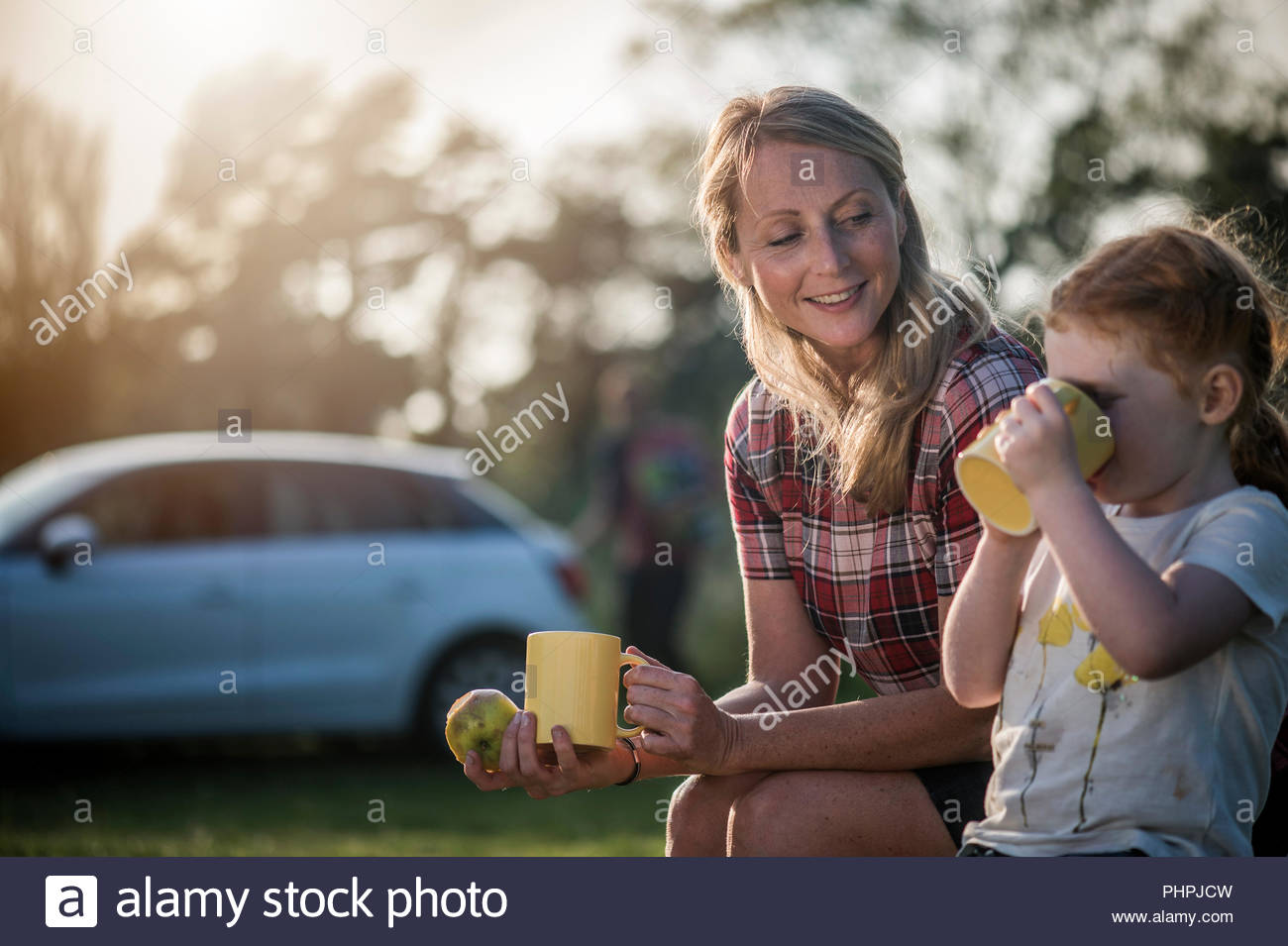 Mother and daughter holding mugs - Stock Image