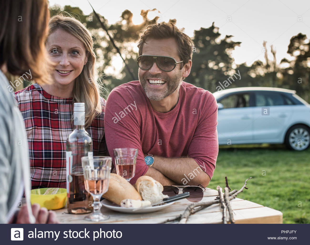 People smiling at picnic table - Stock Image