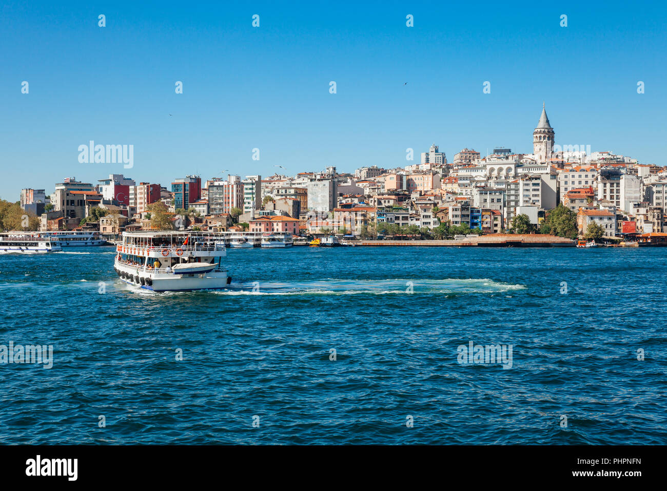 A tourist boat sails across the Golden Horn, Istanbul, Turkey Stock Photo