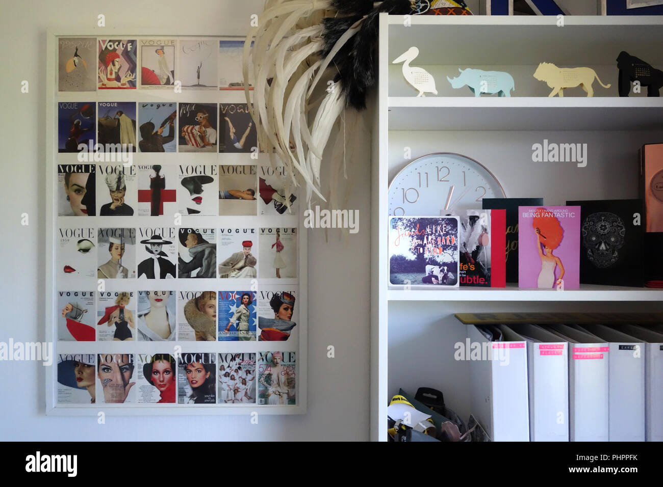 White Contemporary Bookshelf Next To Poster With All The Great Vogue Covers