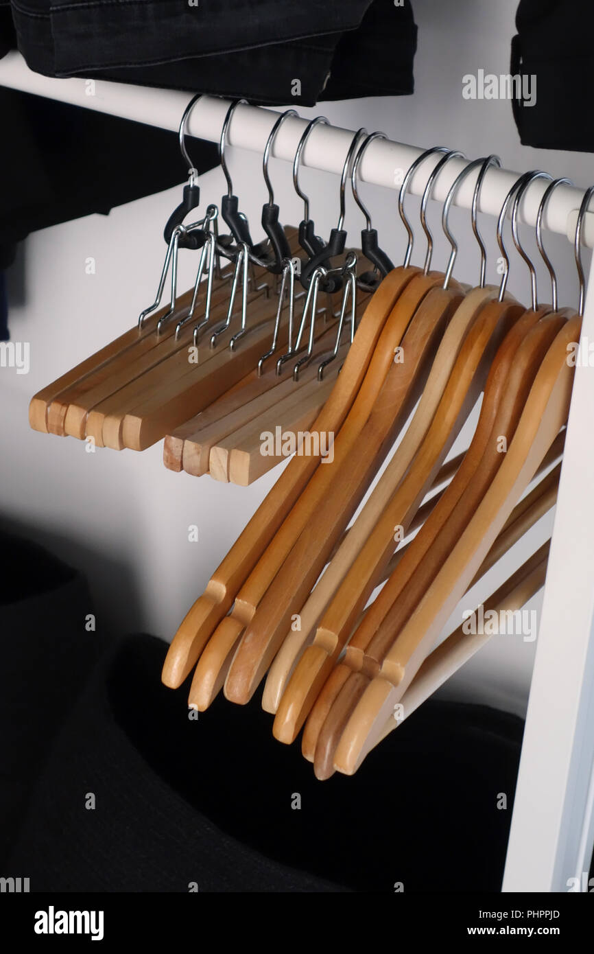 Row of empty Wooden Clothes hangers on a rail - Stock Image