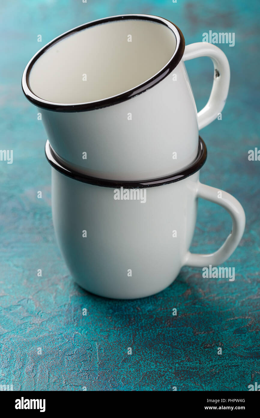 Enamelware on the kitchen table over blue wooden wall - Stock Image
