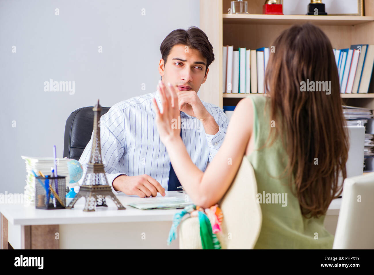 Customer visiting travel agency and talking to agent - Stock Image