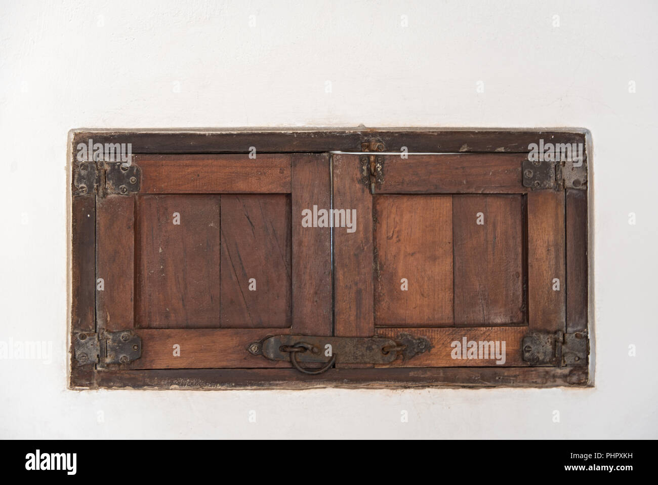 An old wooden shutter in a white wall, Mexico. - Stock Image