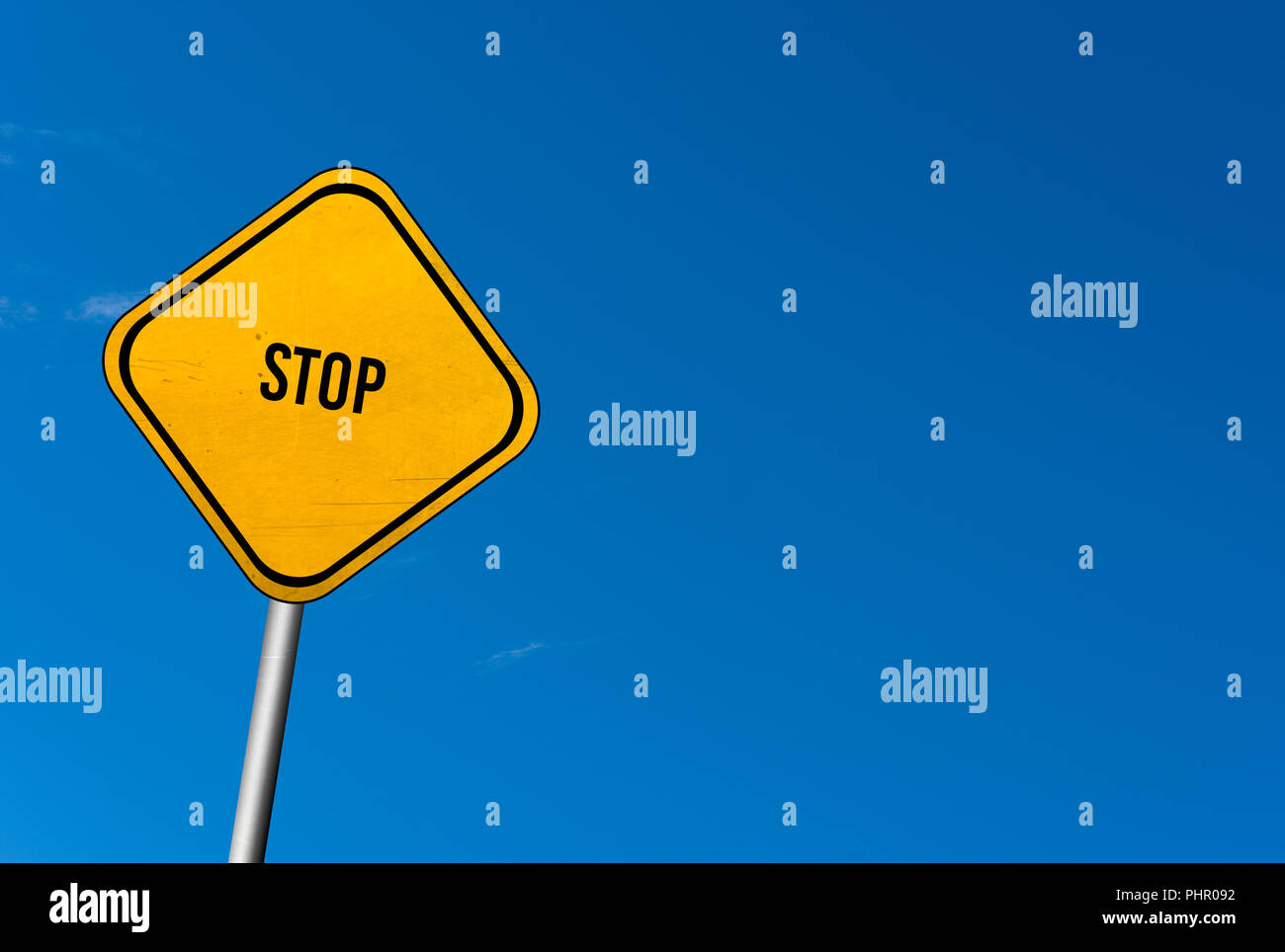 Stop - yellow sign with blue sky - Stock Image