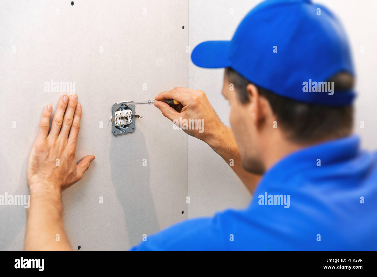 electrician installing electrical outlet on the wall - Stock Image