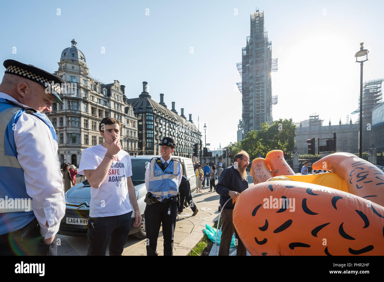 Giant blimp of London Mayor Sadiq Khan wearing a yellow bikini is inflated ready to fly over Parliament square in London, UK. - Stock Image