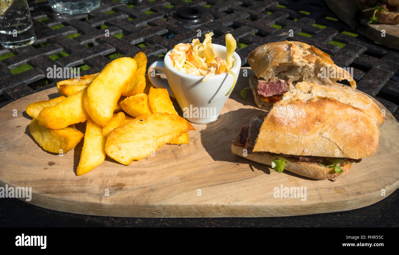 Lunchtime snack Steak  sandwich served on Ciabatta bread coleslaw and Chips - Stock Image