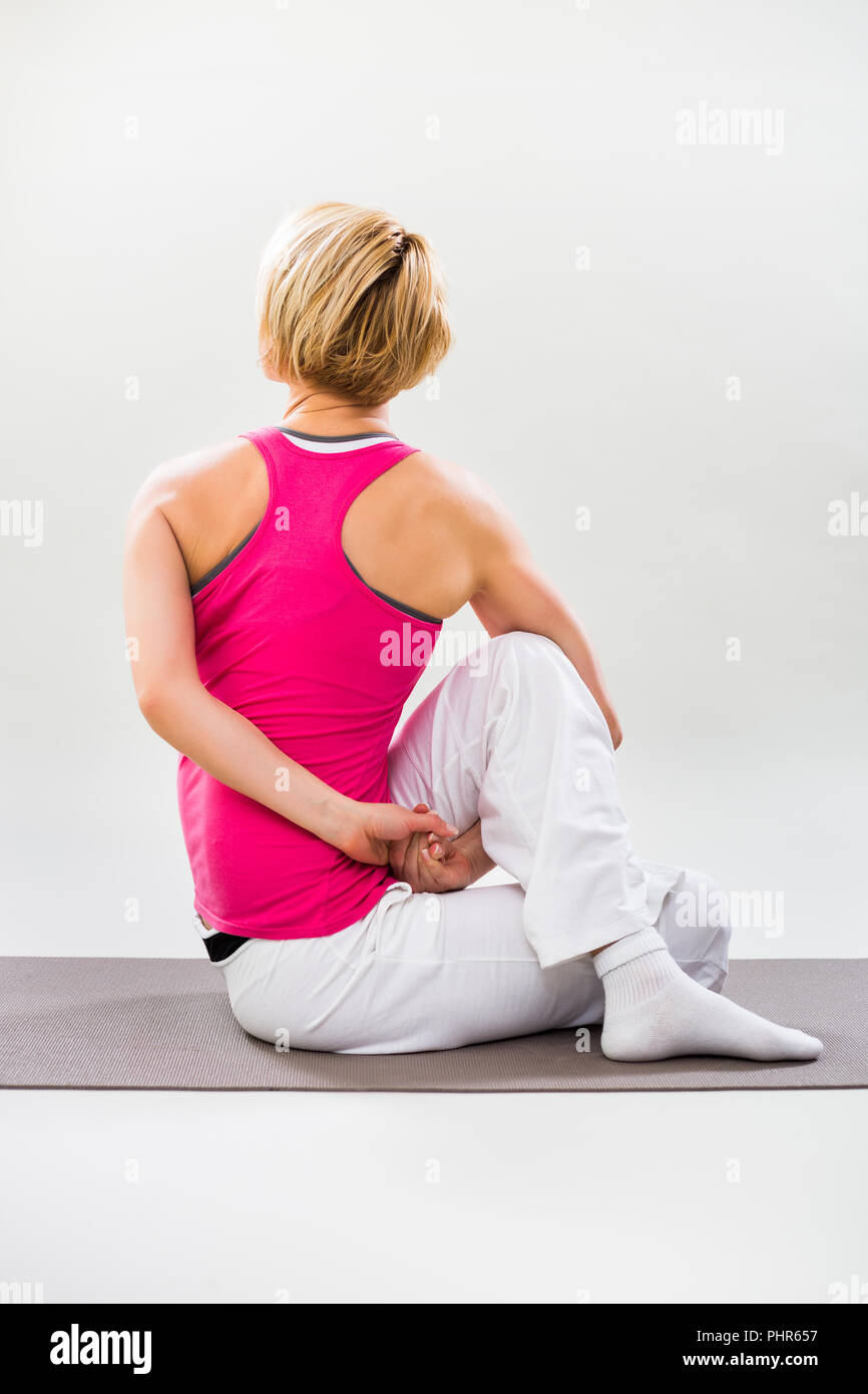 Woman exercising yoga indoor,Spine Twisting Pose/ Matsyendrasana - Stock Image