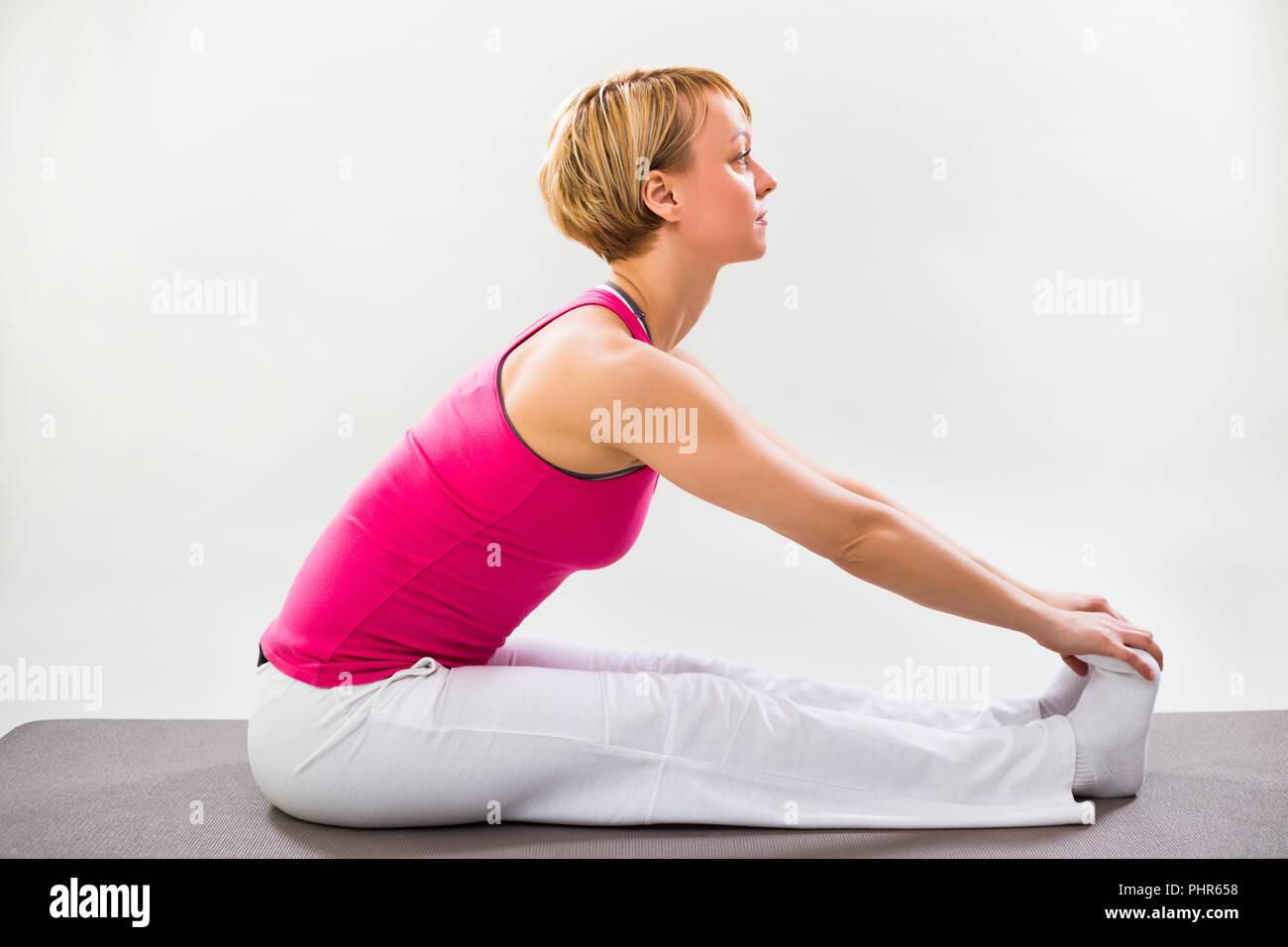 Woman exercising yoga indoor,Seated Forward Bend pose/Paschimottanasana - Stock Image