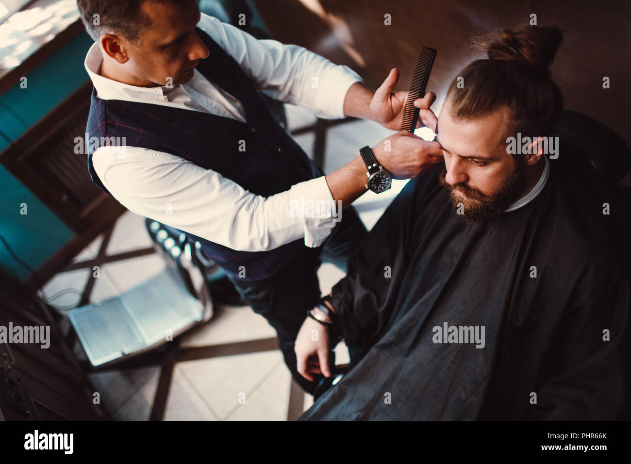 Barbershop with wooden interior. Bearded model man and barber - Stock Image