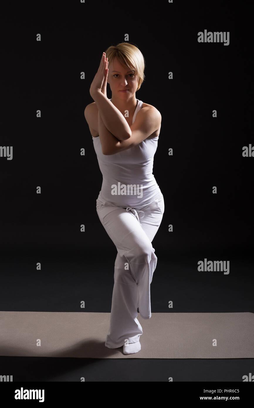 Woman exercising yoga indoor on black background,Eagle pose/Garudasana - Stock Image