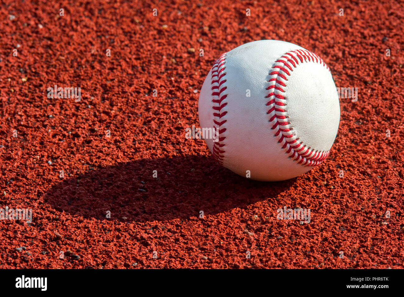 new baseball ball on red track rubber - Stock Image