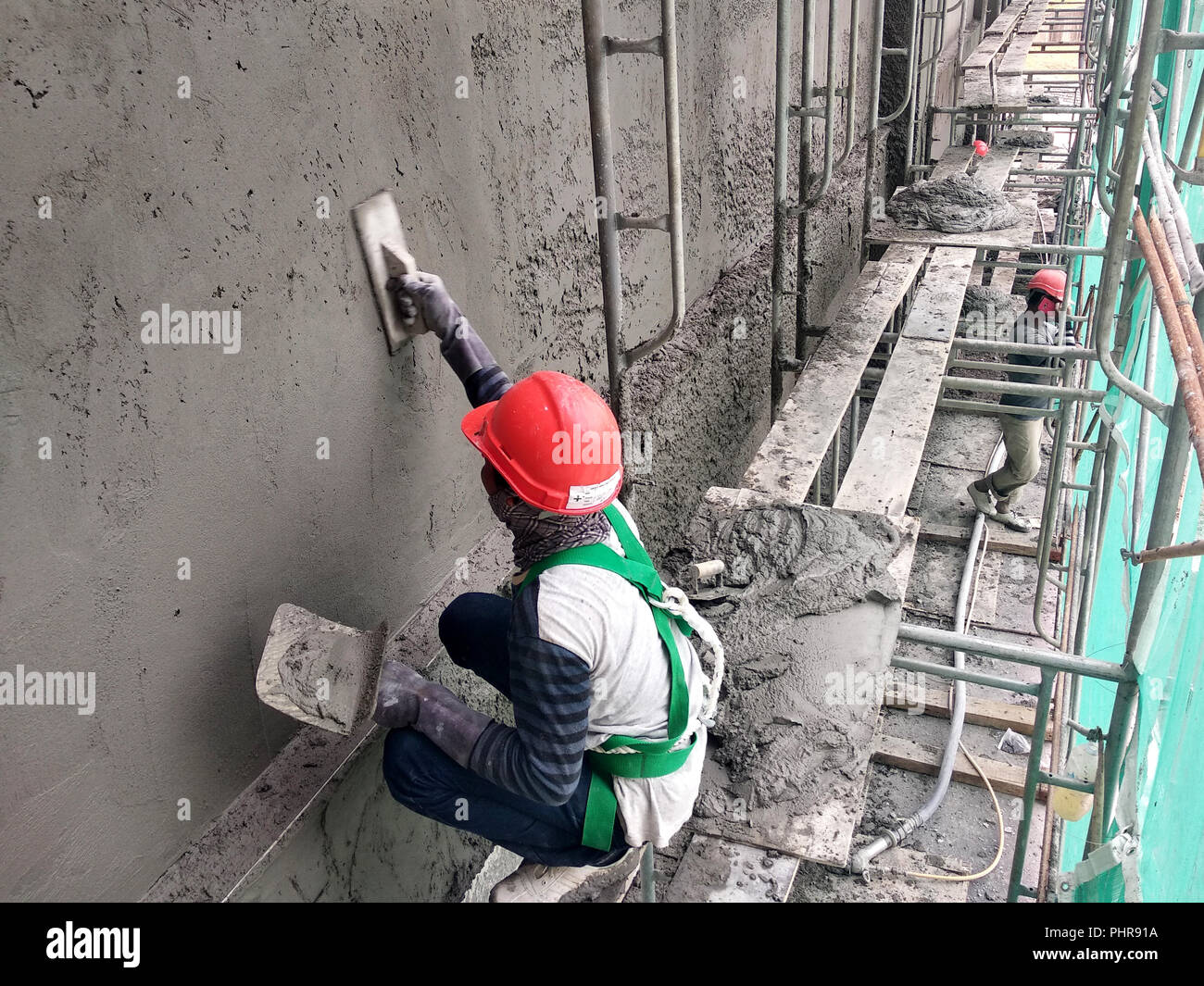 Construction workers plastering wall using cement plaster at the construction site. They are wearing appropriate safety gear to prevent bad happen. - Stock Image