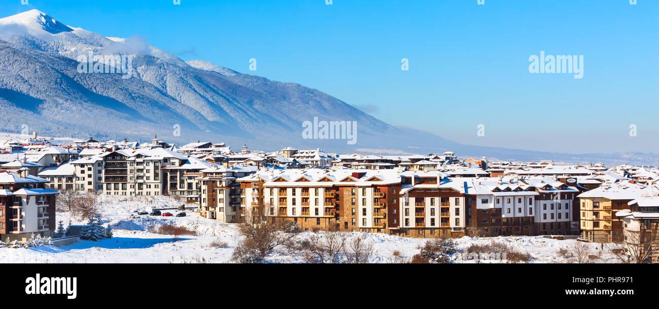 Wooden chalet, houses and snow mountains landscape panorama in bulgarian ski resort Bansko, Bulgaria - Stock Image