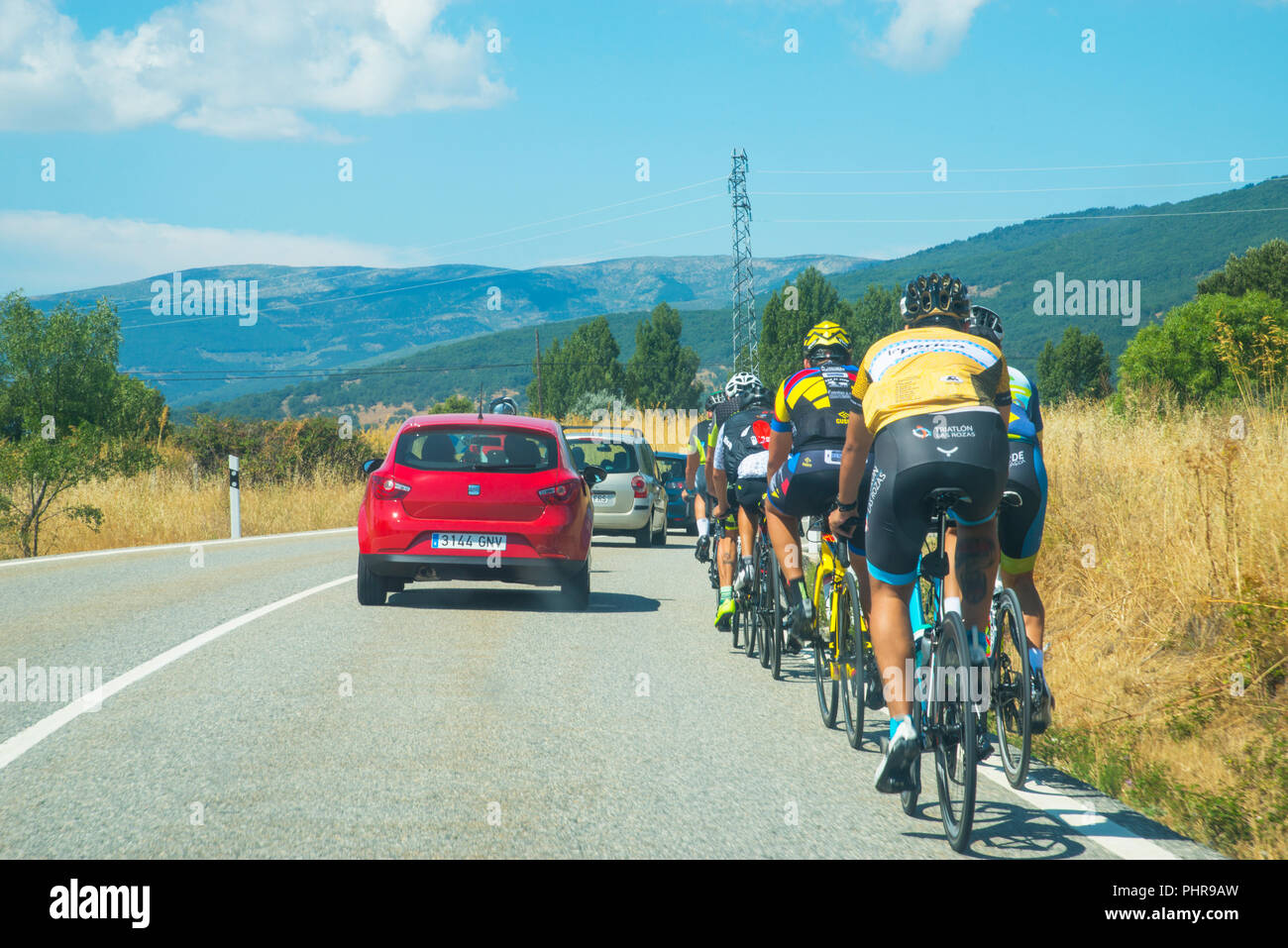 Cars overtaking a group of ciclists. Lozoya, Madrid province, Spain. - Stock Image