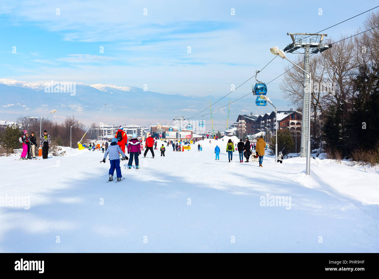 Bansko, Bulgaria - January 13, 2017: Winter ski resort Bansko, attractions, people walking and skiing and mountains view - Stock Image