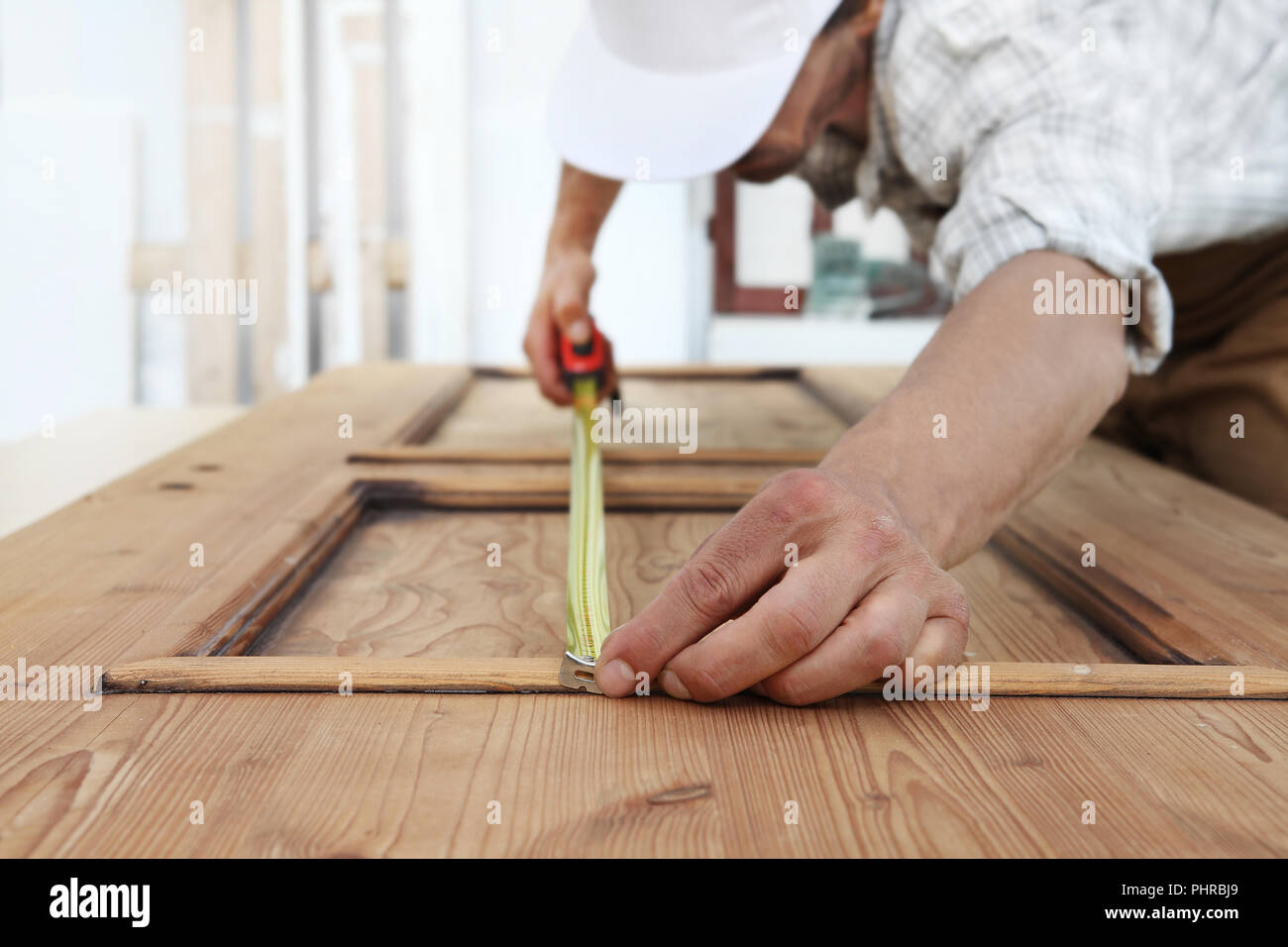 carpenter work the wood, measuring with meter tape a wooden vintage door - Stock Image