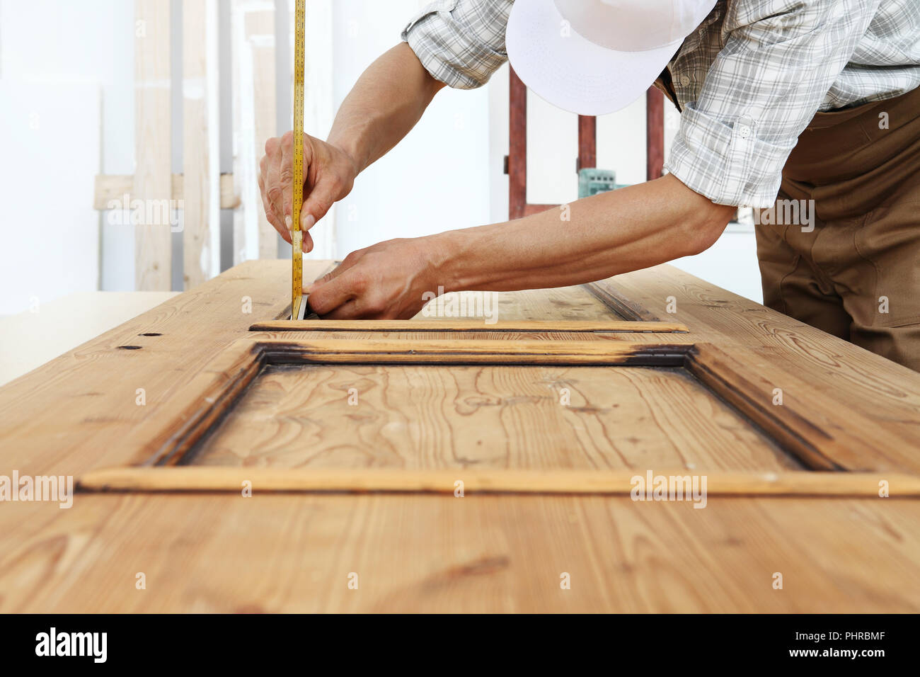 carpenter work the wood, measuring a thickness with angle square on wooden vintage door - Stock Image