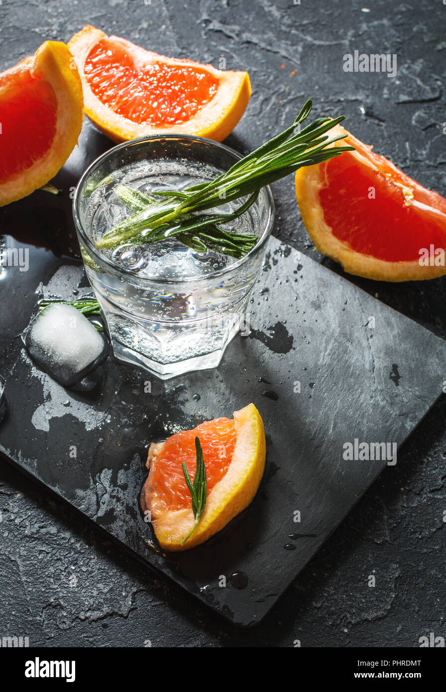 Cocktail with grapefruit, ice and rosemary on dark stone background. - Stock Image