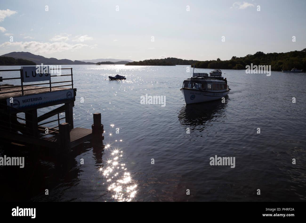 Waterbus approaching Luss pier, Loch Lomond, Scotland, shot into the sun. - Stock Image