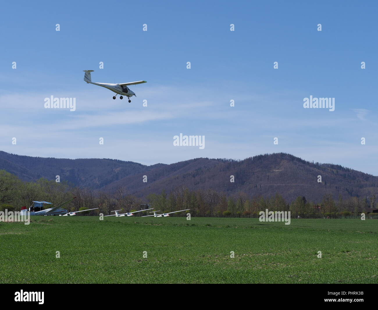 Pipistrel Alpha Trainer airplane lands and four gliders lay on grassy airfield in european Bielsko-Biala city at Poland - Stock Image