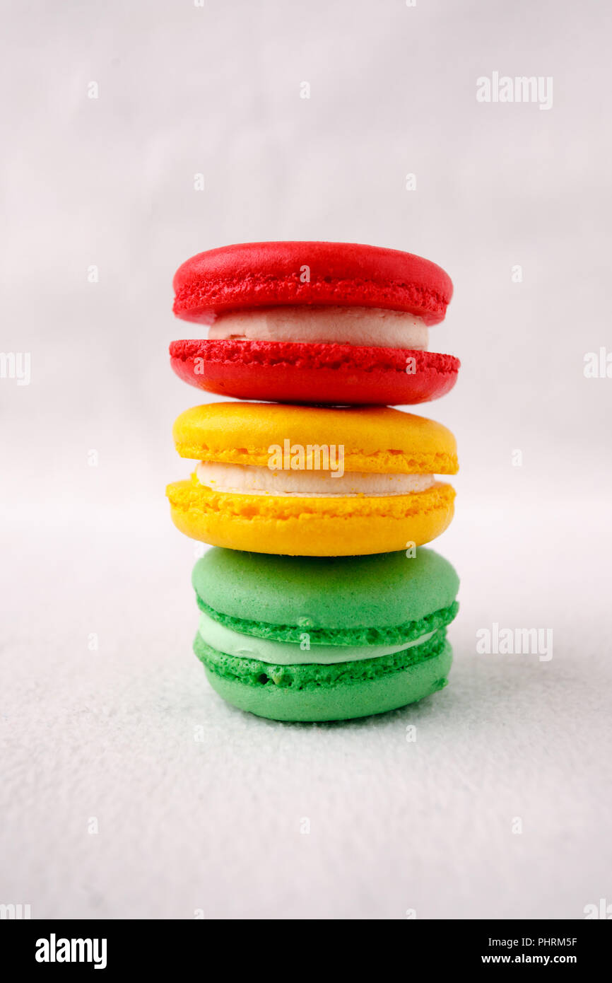 Different kind of macaroons in stack on white background, traffic light sweet conceptual, copy space - Stock Image