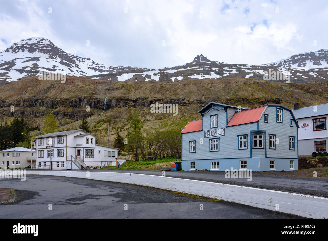 Houses in Seyðisfjörður, Iceland with snow-capped hills in the background - Stock Image