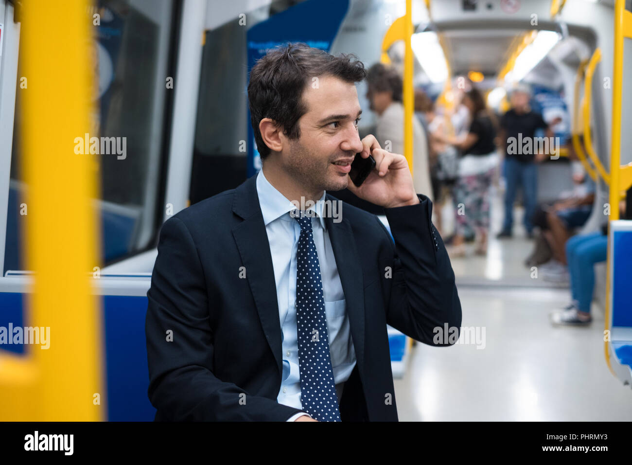 Portrait of businessman talking on his mobile phone while is going to work - Stock Image