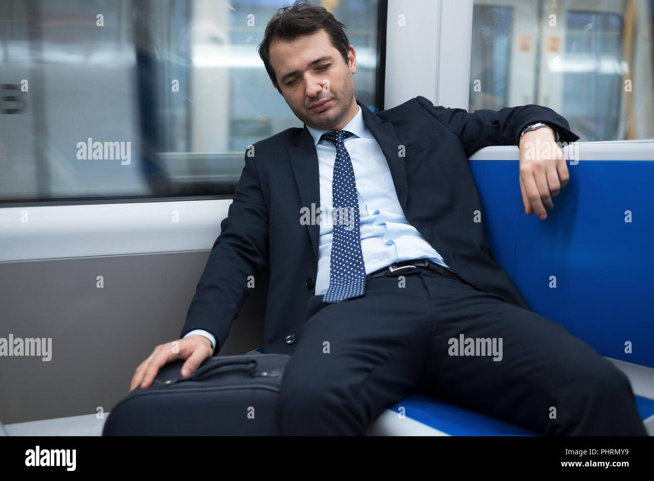 Tired businessman sleeping while going to work - Stock Image