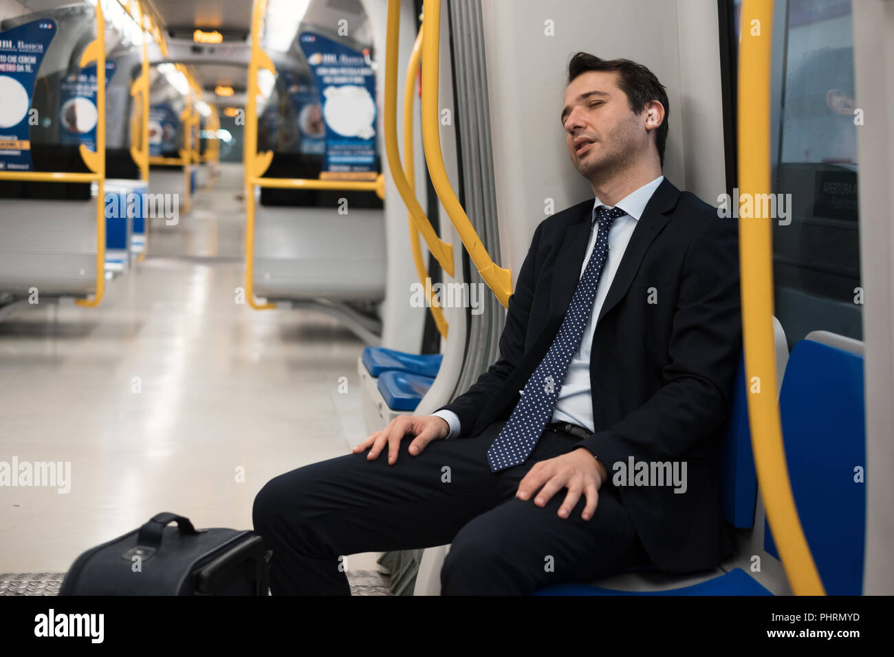 Exhausted commuter portrait sleeping on metro underground - Stock Image