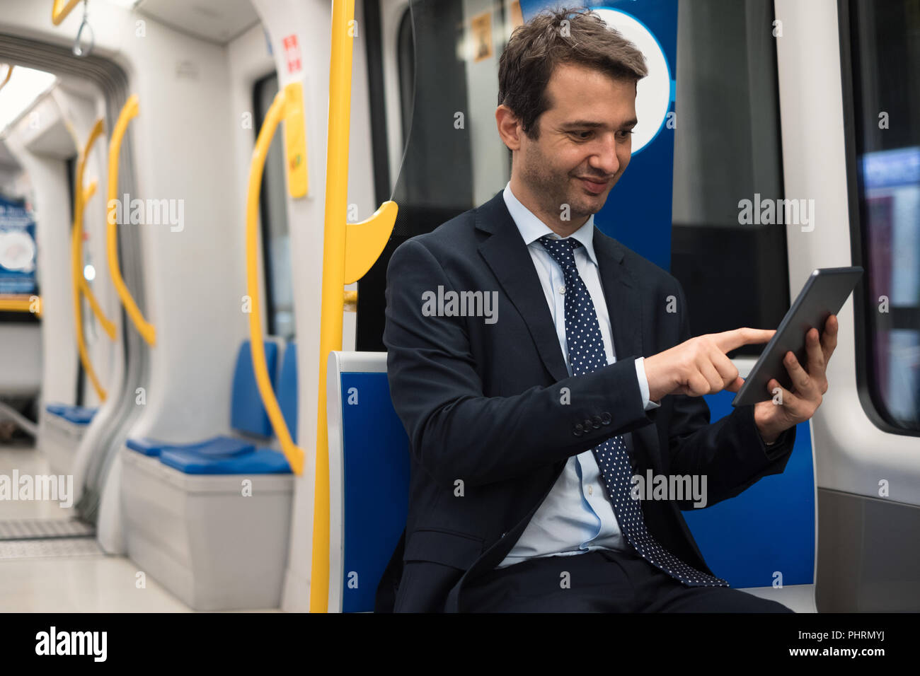 Portrait of businessman watching his digital tablet while is going to work - Stock Image
