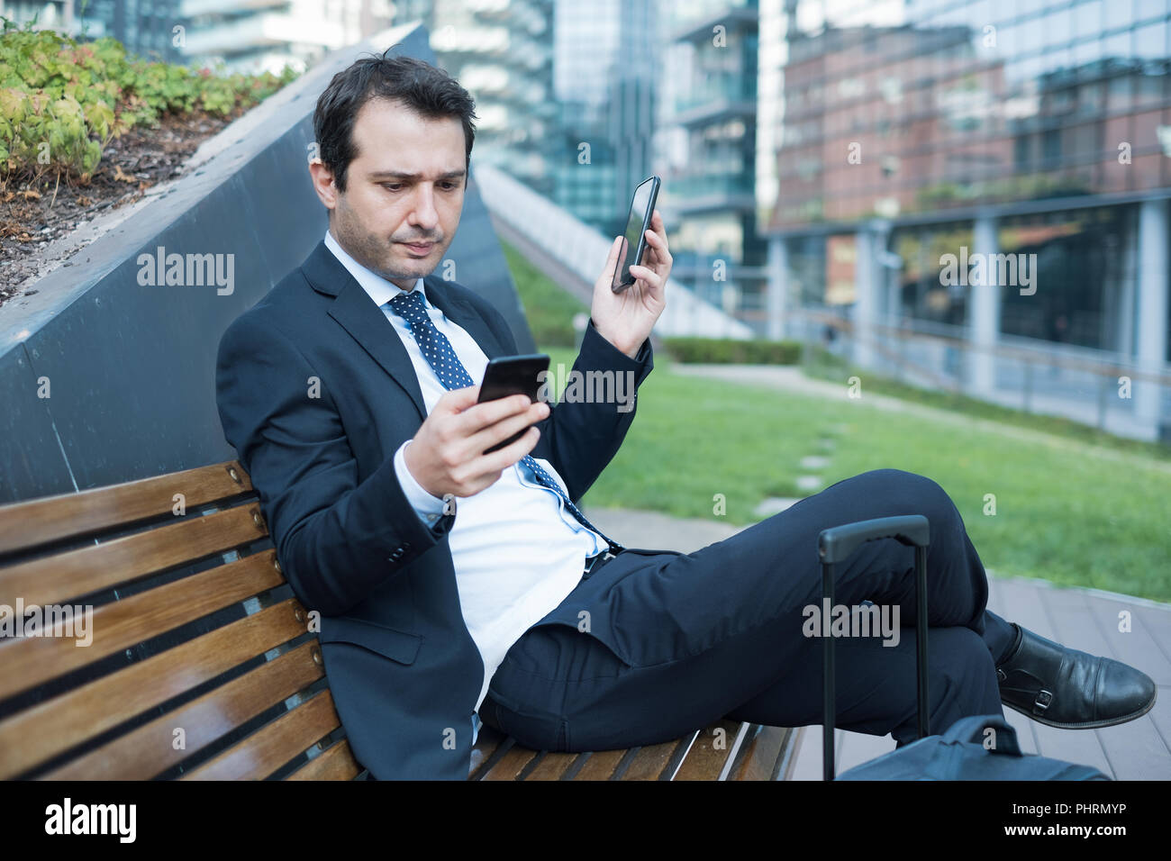 Stressed and multitasking businessman holding two smartphones - Stock Image