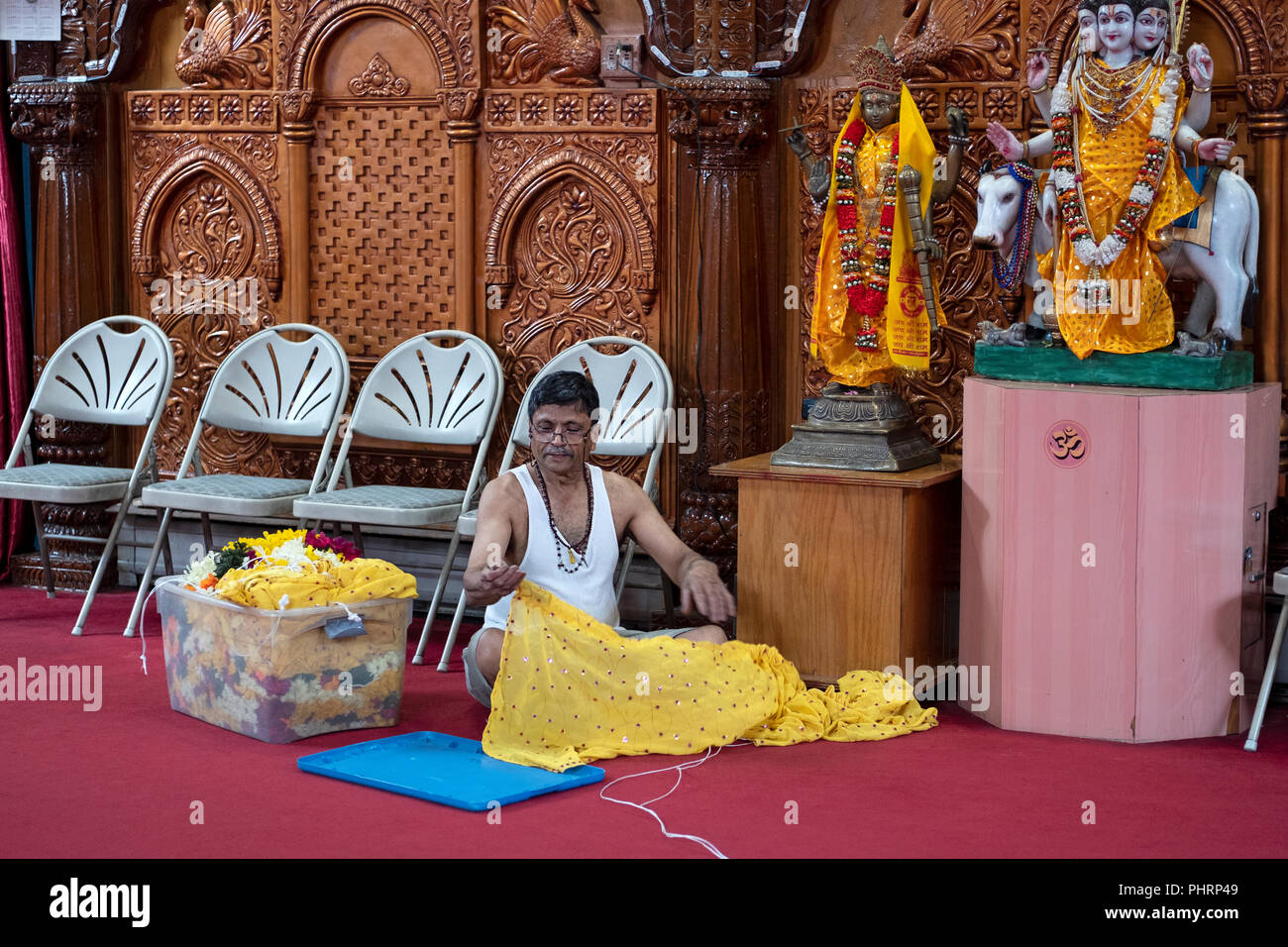 An Indian worker at the Geeta temple sewing costumes that will be put on the statues of the deities. In Queens, New York City. - Stock Image