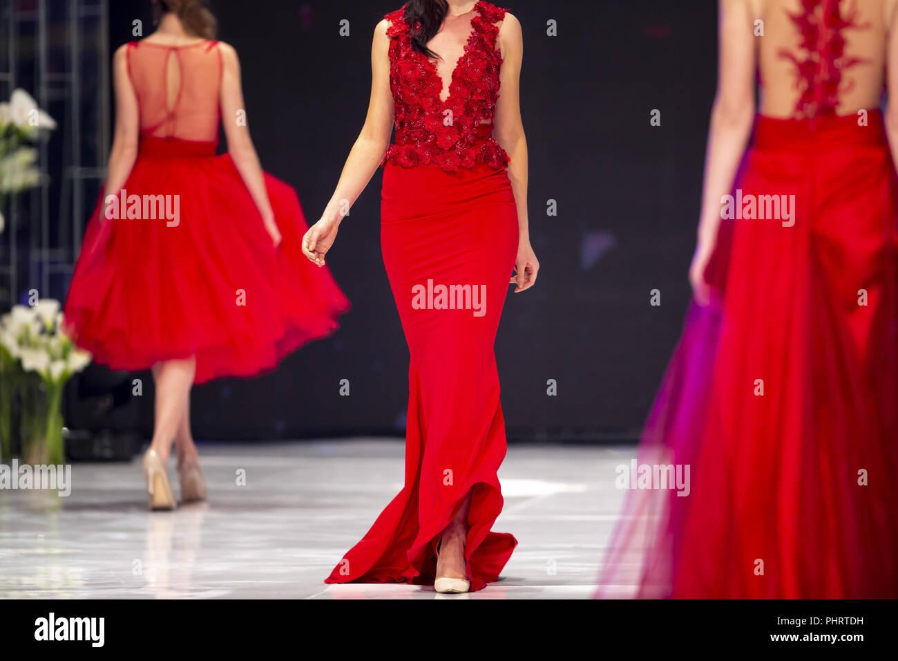 Fashion catwalk runway show models red dress - Stock Image