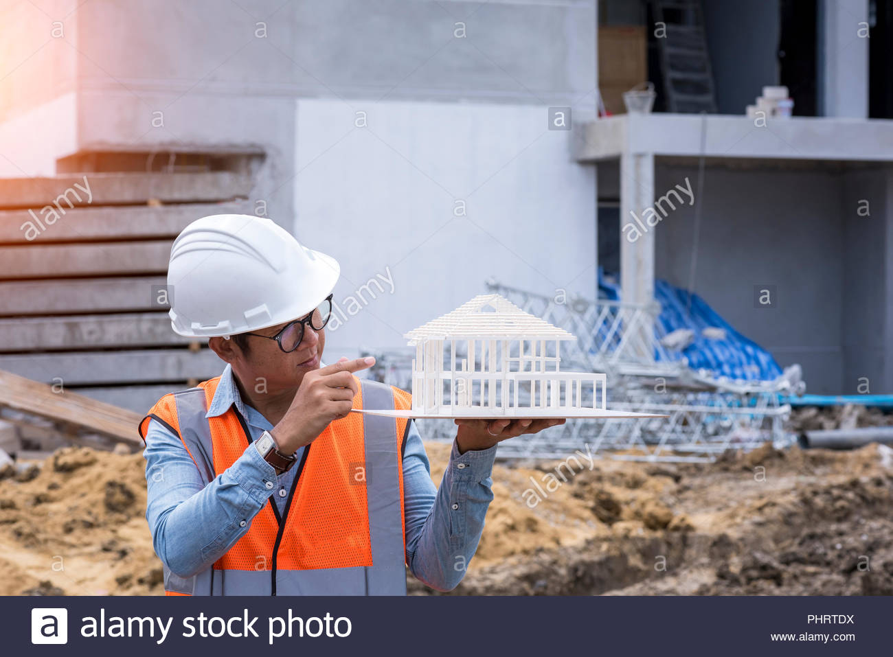 Architect civil engineer working at construction site and checking building model Stock Photo