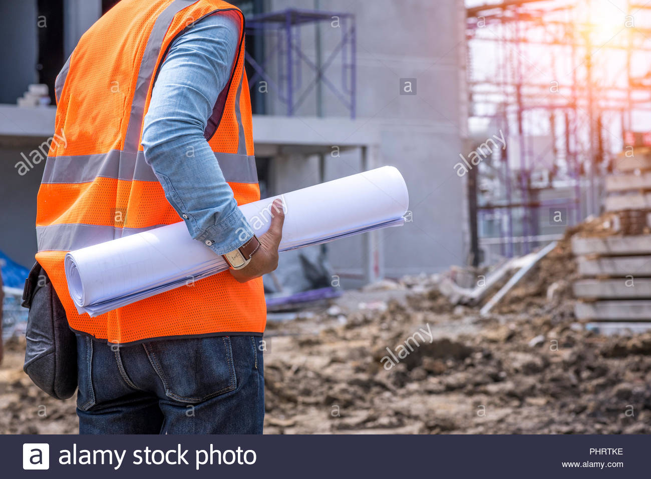 Civil engineering construction inspector with blueprint at construction site - Stock Image