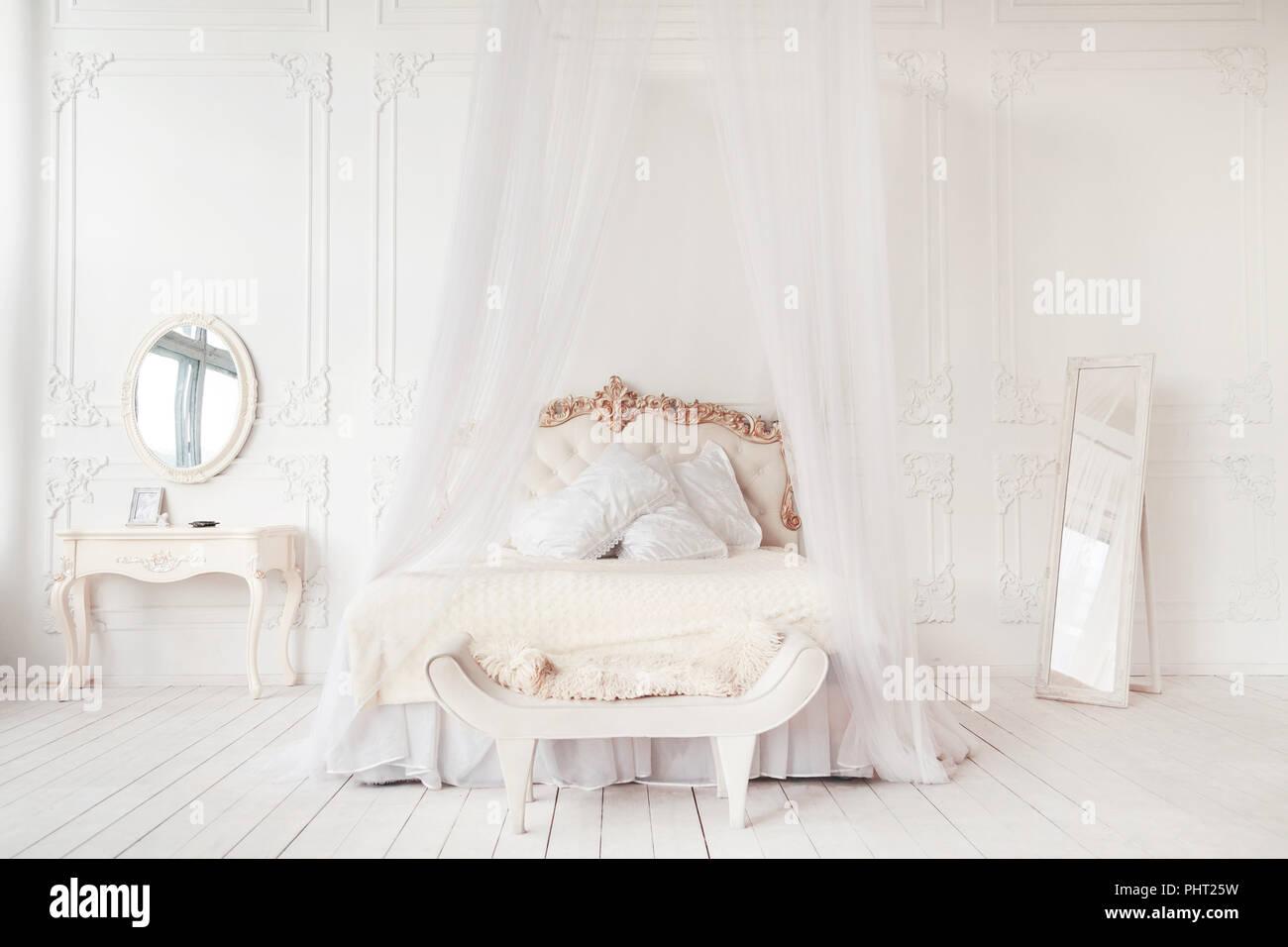 bedroom in soft light colors. big comfortable double bed in elegant classic bedroom Stock Photo