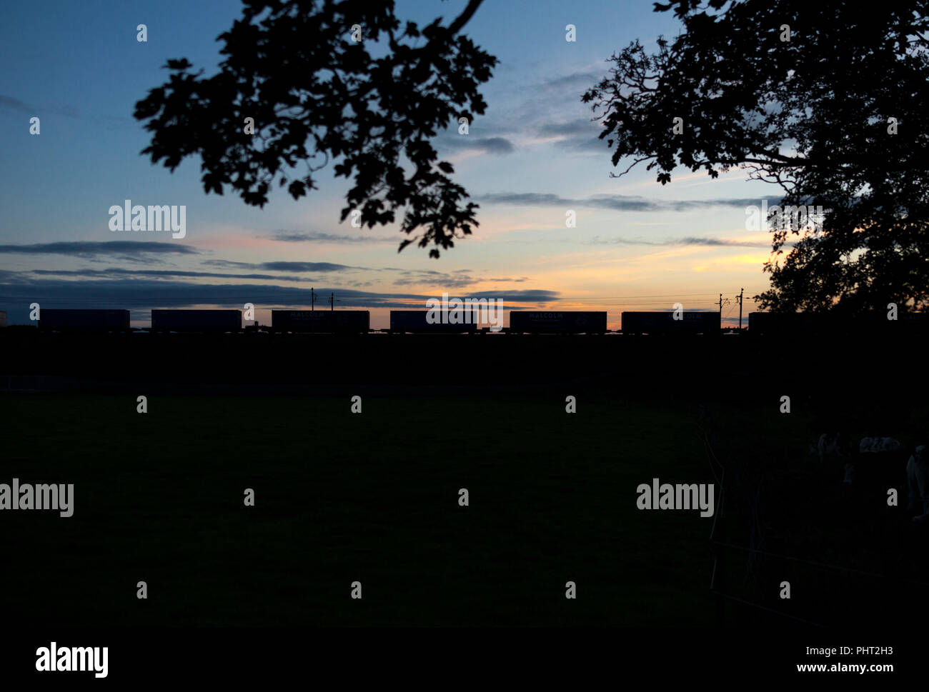 Containers on a DB Cargo intermodal container train making a silhouette at sunset on the west coast main line. - Stock Image