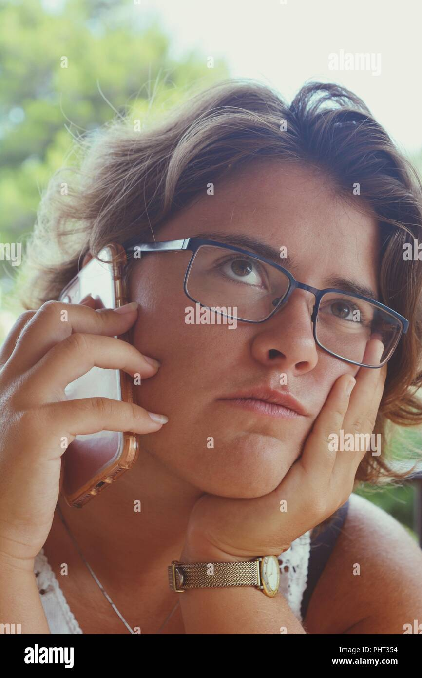 Millennial woman, with mobile phone in hand, listening, with eyes raised and a bored / dubious expression - Stock Image
