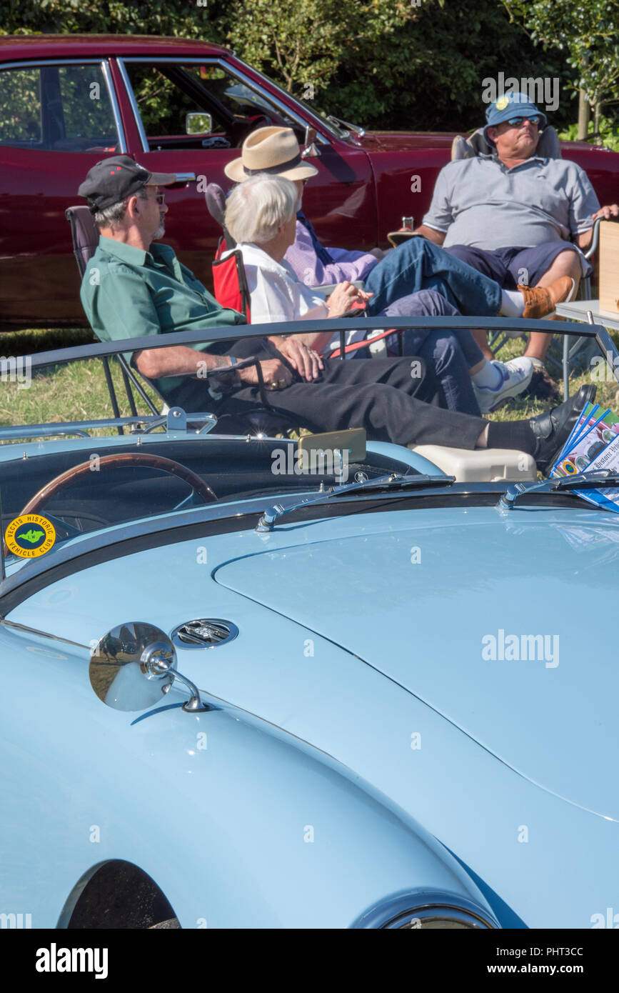 classic and vintage car enthusiasts at a motor or collectors car show in the sunshine. - Stock Image