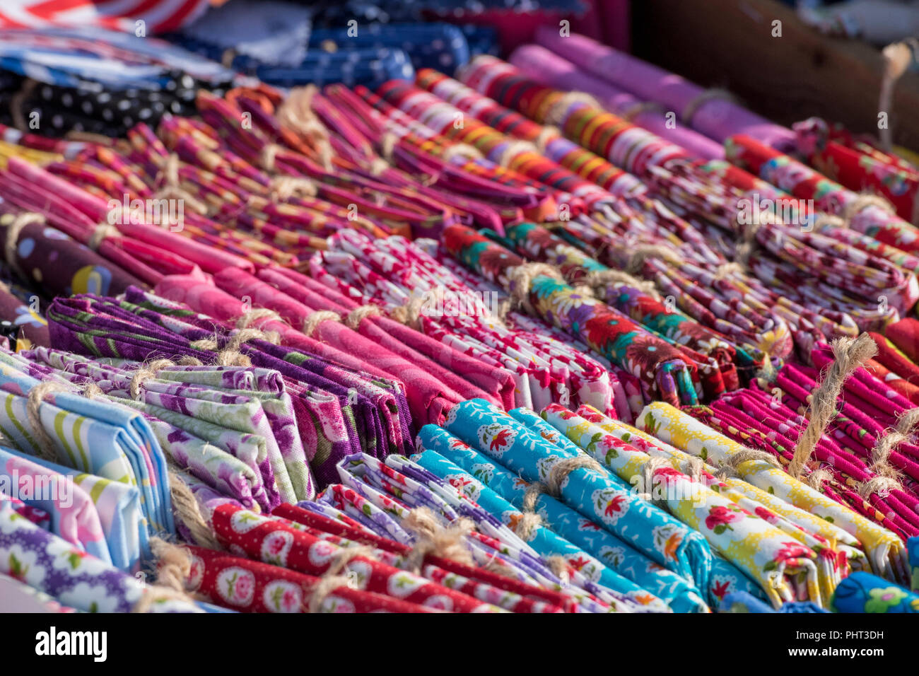 a selection of multi-coloured linen or cotton throws and cloths on sale on a rack at a market stall selling colourful linen. - Stock Image